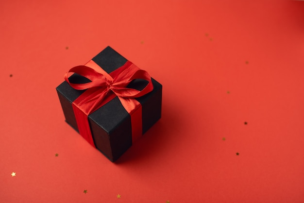 Caja de regalo negra atada con la cinta roja sobre rojo. concepto de san valentín.