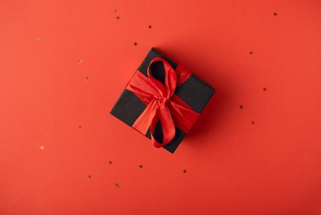 Caja de regalo negra atada con la cinta roja sobre rojo. vista superior. concepto de san valentín.