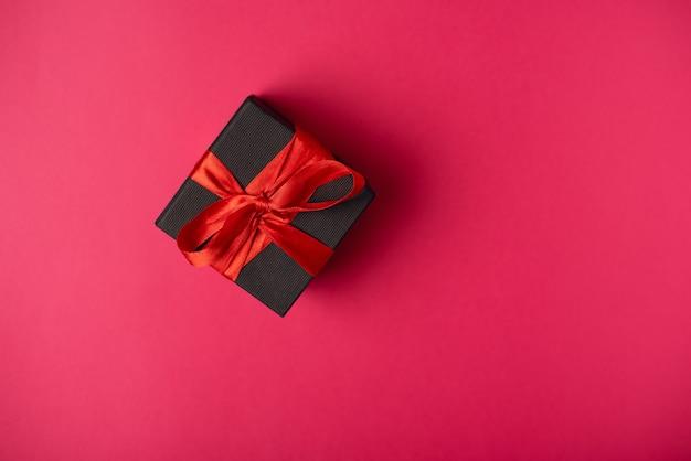 Caja de regalo negra atada con una cinta roja. vista plana endecha, superior.