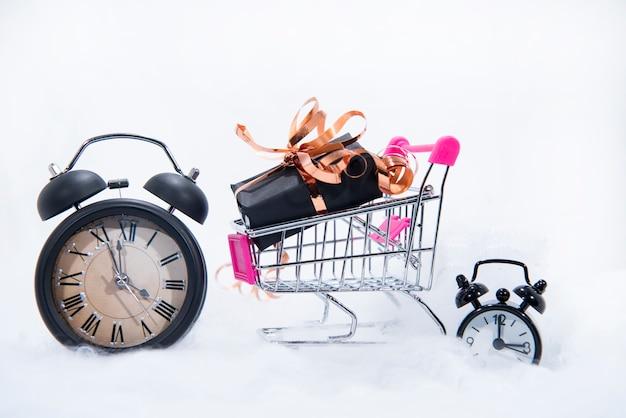 Caja de regalo negra con cinta dorada en pequeño carrito de compras y reloj despertador