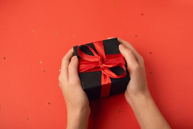 Caja de regalo negra con cinta roja en manos de mujer en rojo. concepto de san valentín.