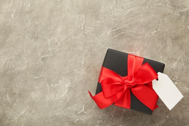 Caja de regalo negra con etiqueta de venta en hormigón gris