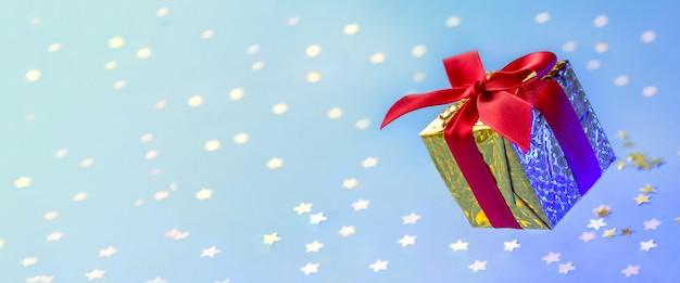 Caja de regalo de oro de banner con cinta roja flotando sobre fondo azul con estrellas brillantes