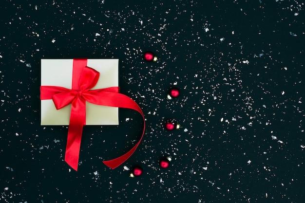 Caja de regalo de oro con un lazo de satén rojo sobre negro nevado