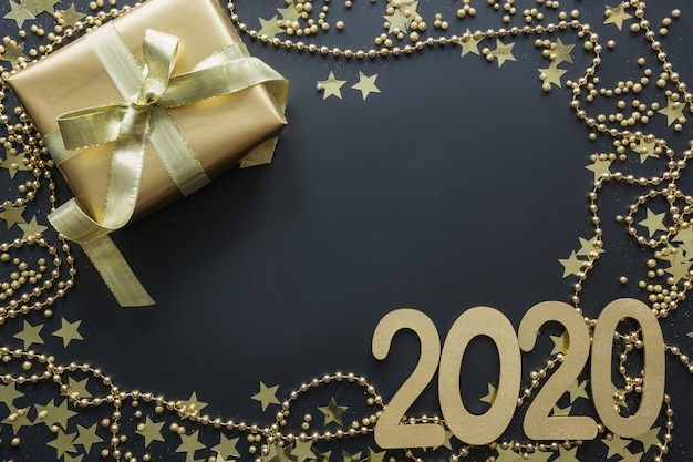 Caja de regalo de oro de lujo con fecha 2020 sobre fondo negro navidad boxing day flat lay xmas. año nuevo.