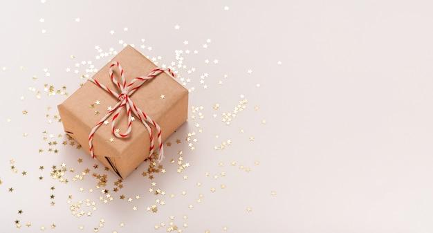 Caja regalo en papel artesanal con cinta de año nuevo blanco-rojo y estrellas de caramelo doradas sobre fondo beige