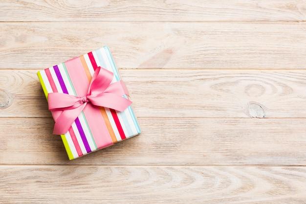 Caja de regalo de papel con cinta de color sobre fondo de madera naranja. vista superior con espacio de copia concepto de vacaciones de navidad