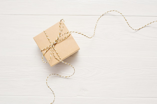 La caja de regalo en papel kraft con un lazo de cuerda está sobre una mesa de madera blanca, con lugar para el texto.