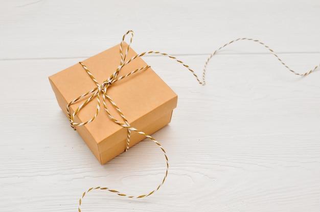 La caja de regalo en papel kraft con un lazo de cuerda está sobre una mesa de madera blanca