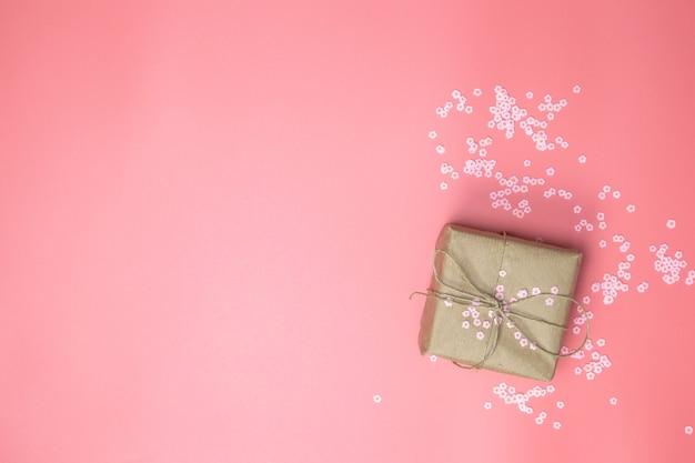 Caja de regalo con papel kraft marrón rodeada de margaritas rosas y fondo rosa flatlay, primavera