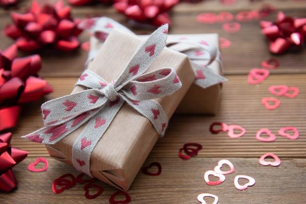 Caja de regalo de papel marrón kraft con lazos rojos y confeti, en mesa de madera. san valentín, cumpleaños.