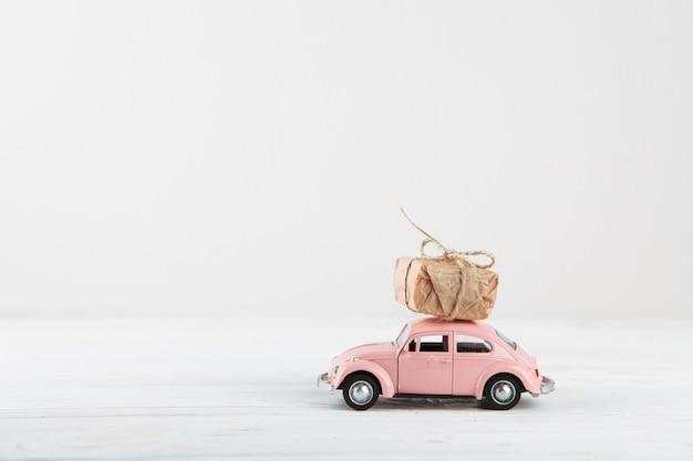 Caja de regalo pequeña en coche de juguete rosa