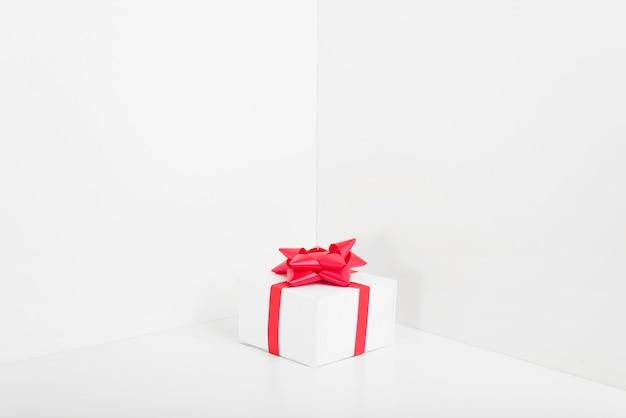 Caja de regalo pequeña con lazo en la mesa.