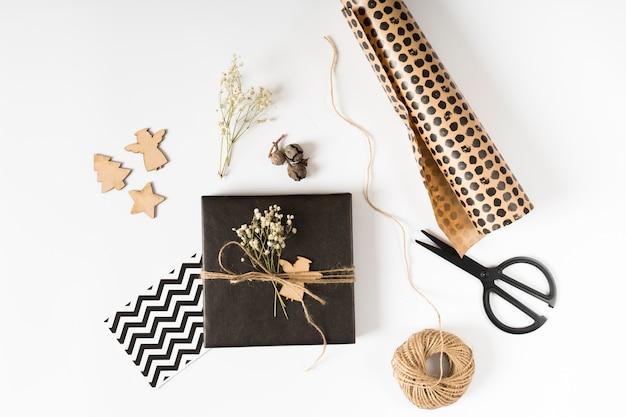 Caja de regalo pequeña con papel de regalo en mesa.
