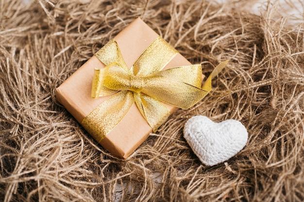 Caja de regalo con pequeño corazón blando en mesa.