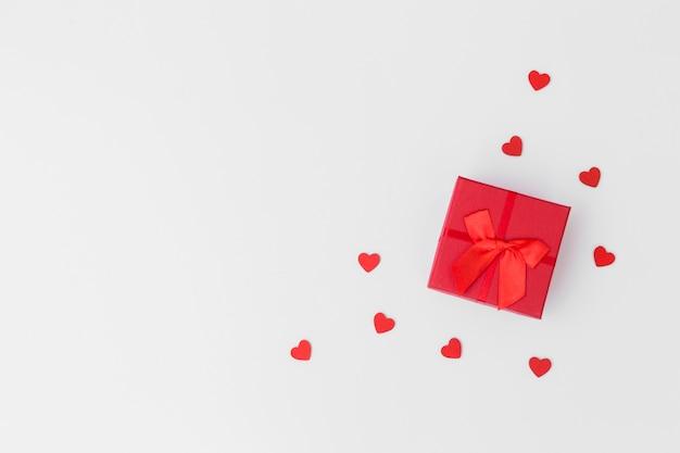 Caja de regalo con pequeños corazones en mesa.