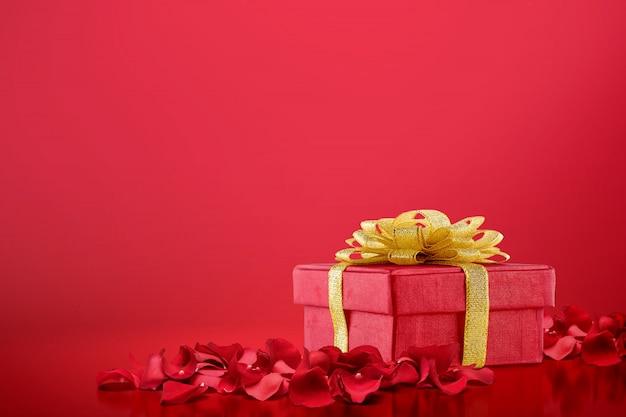 Caja de regalo y pétalos de rosas rojas sobre un fondo rojo.