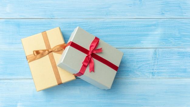 Caja de regalo de plata y oro sobre una mesa de madera azul.