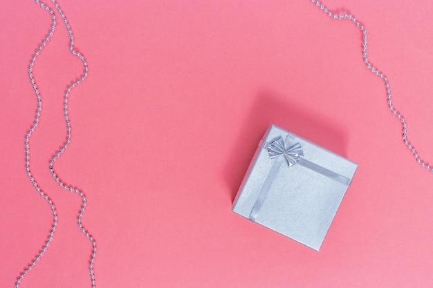 Caja de regalo plateada. composición del día de san valentín en papel rosa