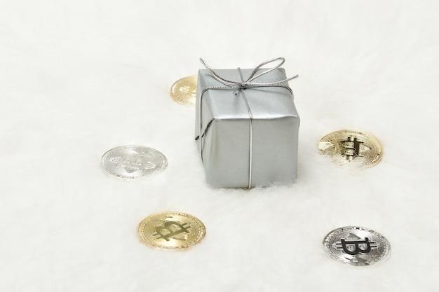 Caja de regalo plateada y monedas bitcoins sobre un fondo blanco.