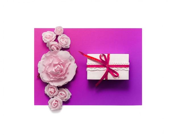 Caja de regalo presente decoraciones flatlay. cinta de regalo rosa flores blancas vista superior