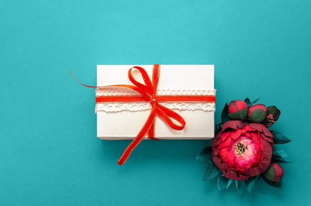 Caja de regalo presente decoraciones flatlay. regalo blanco cinta rosa flores vista superior.