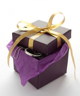 Caja de regalo púrpura con joyas y cinta amarilla sobre blanco
