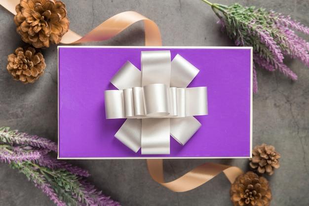 Caja de regalo púrpura sobre fondo de cemento