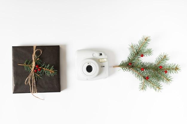Caja de regalo con rama de abeto y cámara.