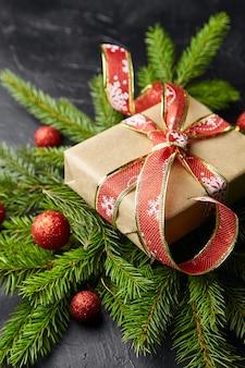 Caja de regalo con rama de árbol de navidad verde y bolas rojas sobre fondo negro