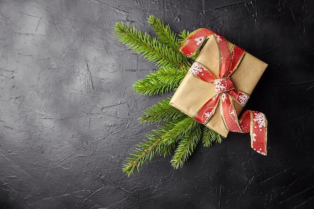 Caja de regalo con rama de árbol de navidad verde sobre fondo oscuro con vista superior del espacio de copia