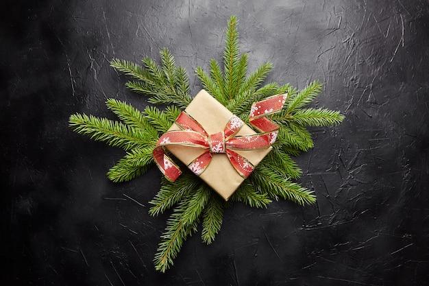 Caja de regalo con rama de árbol de navidad verde sobre fondo oscuro vista superior