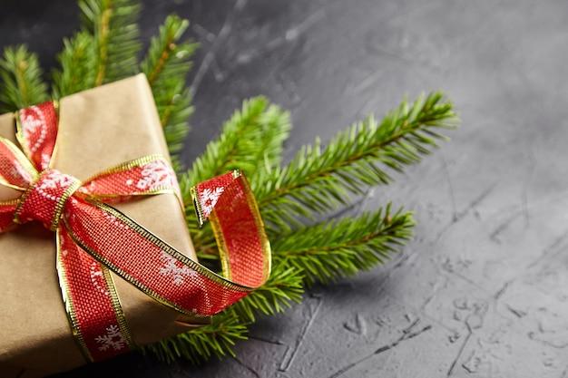 Caja de regalo con rama de árbol de navidad verde sobre fondo oscuro