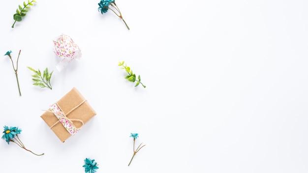 Caja de regalo con ramas de flores en mesa blanca