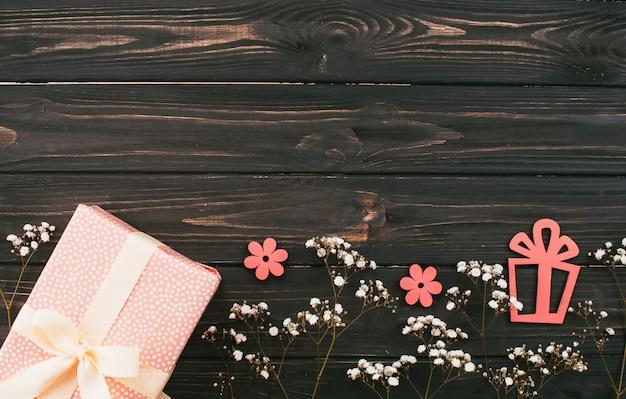 Caja de regalo con ramas de flores en mesa de madera.