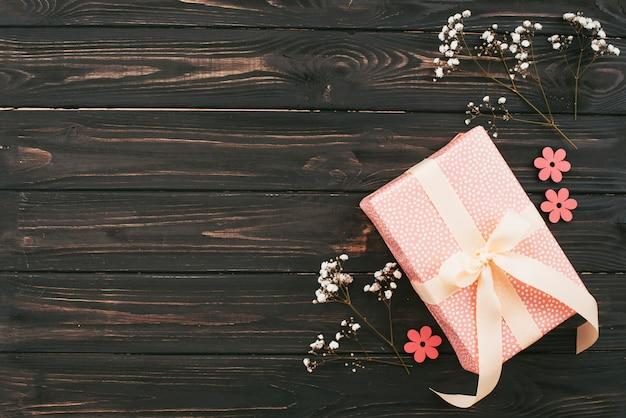 Caja de regalo con ramas de flores en mesa