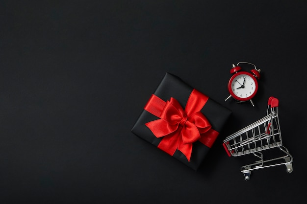 Caja de regalo, reloj despertador y carro de la tienda en negro
