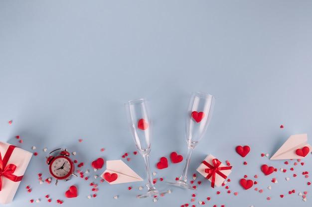 Caja de regalo, reloj despertador, corazones de caramelo rojo y avión de papel, dos copas de champán en mesa azul pastel.