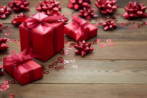 Caja de regalo roja con arcos, en mesa de madera. copia espacio san valentín, cumpleaños, navidad.