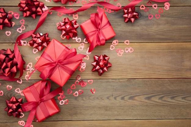 Caja de regalo roja con arcos, sobre fondo de madera. copia espacio san valentín, cumpleaños, navidad.