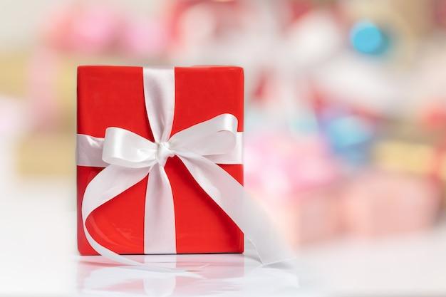 Una caja de regalo roja con una cinta blanca sobre la mesa y borrosa para cualquier concepto de vacaciones