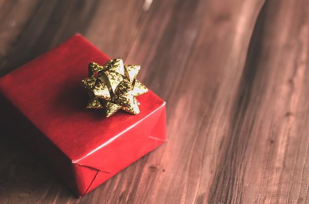 Caja de regalo roja y cinta dorada en madera.