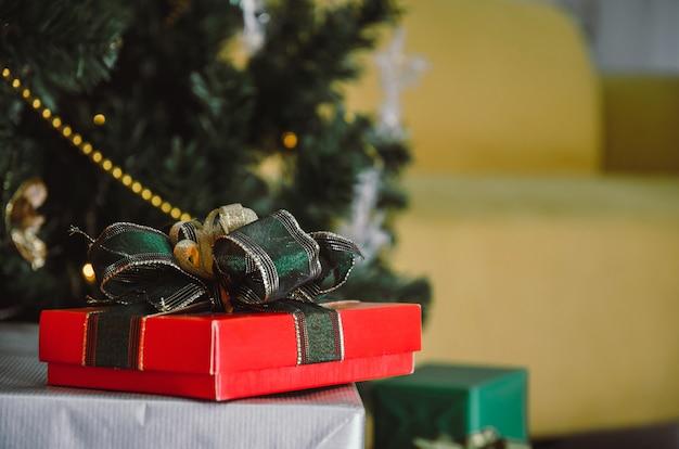 Caja de regalo roja con cinta verde en el escritorio con árbol de navidad