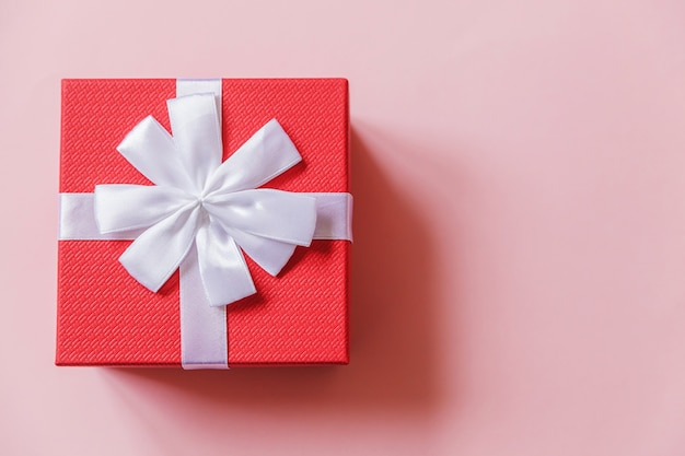 Caja de regalo roja de diseño simplemente minimalista aislada sobre fondo de colores rosa pastel