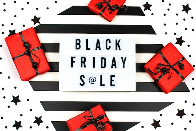 Caja de regalo roja envuelta y atada con fondo de banner de lazo negro