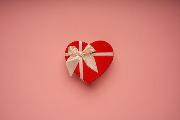 Caja de regalo roja, en forma de corazón, atada con una cinta sobre el fondo rosa, felicitaciones, regalo, vacaciones, sorpresa
