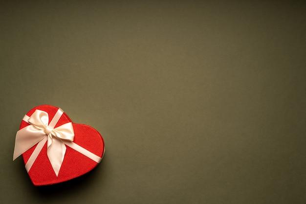 Caja de regalo roja, en forma de corazón, atada con una cinta sobre el fondo verde, felicitaciones, regalo, vacaciones, sorpresa