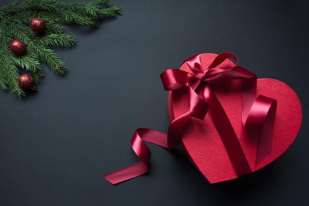 Caja de regalo roja en forma de corazón con cinta roja y ramas de árbol de navidad decoradas