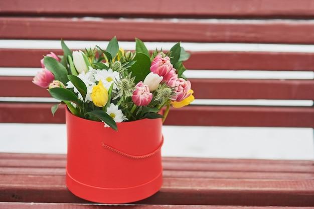 Caja de regalo roja con hermoso ramo símbolo de mujer romántica