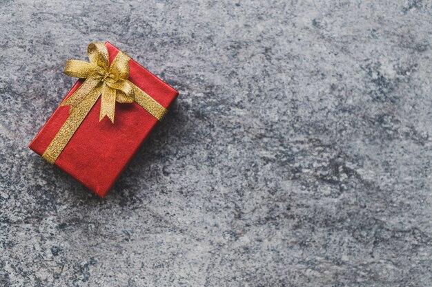 Caja de regalo roja y un lazo dorado colocado sobre una mesa de piedra gris.
